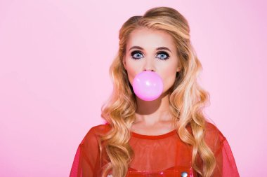 beautiful girl blowing bubble gum isolated on pink, doll concept