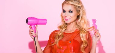 panoramic shot of beautiful girl with hair dryer and hair brush on pink, doll concept