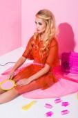 schöne Mädchen sitzen mit Handspiegel auf rosa, Puppe Konzept