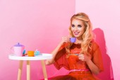 beautiful smiling girl with toy cup on pink, doll concept