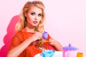 beautiful girl with toy cup looking at camera on pink, doll concept