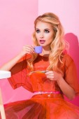schöne Mädchen posiert mit Spielzeug-Tasse auf rosa, Puppe Konzept