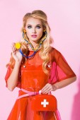Photo beautiful girl with first aid kit and stethoscope on pink, doll concept