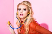 krásná dívka se stetoskem na růžovém, panenku