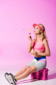 girl in sportswear sitting on boombox and blowing soap bubbles on pink, doll concept