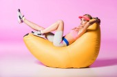 beautiful girl in sun visor hat sitting on bean bag chair on pink, doll concept