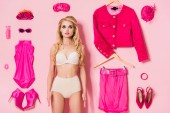 pretty girl in underwear near flat lay of clothes and accessories on pink, doll concept
