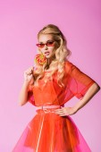 beautiful girl in sunglasses posing with lollipop on pink, doll concept