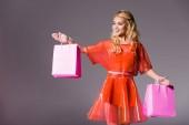 schönes Mädchen mit Einkaufstaschen auf grau, Puppenkonzept