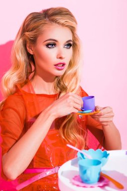 beautiful stylish girl with toy cup on pink, doll concept