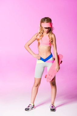 beautiful girl in sportswear posing with penny board on pink, doll concept