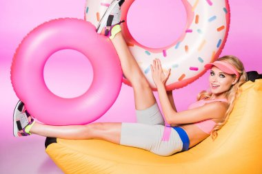 attractive happy girl on bean bag chair with inflatable swim rings on pink, doll concept