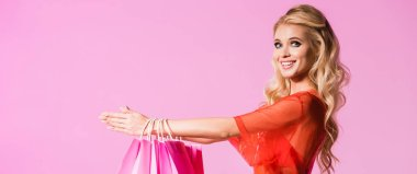 panoramic shot of beautiful girl with shopping bags isolated on pink, doll concept