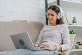 krásná a brunetka se sluchátky s úsměvem a pohledem na obrazovku přenosného počítače
