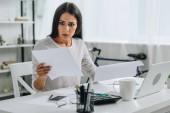 schockierte und attraktive Frau sucht und hält Papiere in Wohnung