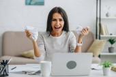 Křičící a atraktivní žena, která se dívá na kameru a přidržává papíry
