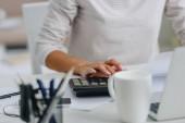 oříznutý pohled ženy v bílém Jersey pomocí kalkulačky v bytě