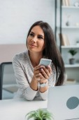 attractive and brunette woman holding smartphone and looking away