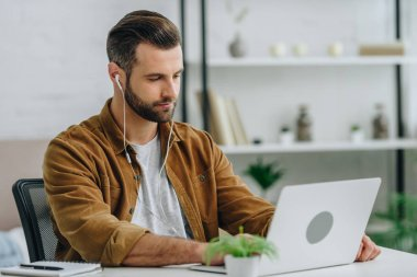 handsome man using laptop and listening music in apartment