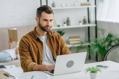 handsome man using laptop and looking away in apartment