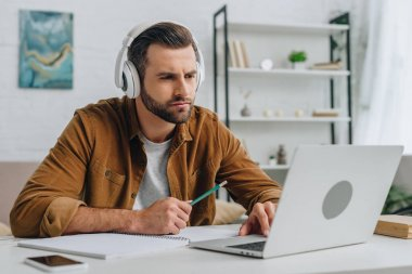 good-looking man listening music, holding pencil and using laptop