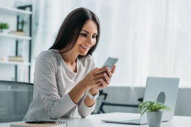 attractive and brunette woman smiling and using smartphone in apartment