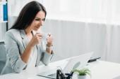krásná a brunetka ve formálním opotřebení s šálkem kávy a pohledem na obrazovku přenosného počítače