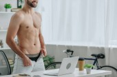 cropped view of man with naked torso dressing up in front of laptop