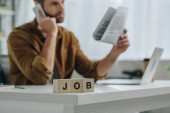 válogatós összpontosít-ból fából készült kocka-val betűk munka és ember beszélő-ra smartphone-ra háttér