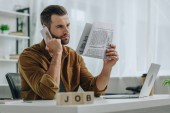 selective focus of wooden cubes with lettering job and man talking on smartphone and holding newspaper