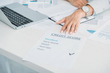 cropped view of woman showing credit score at office
