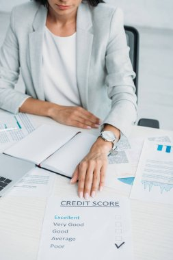 Cropped view of woman in suit showing credit score at office stock vector