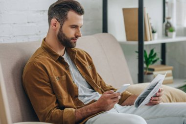 handsome man sitting on sofa, using smartphone and holding newspaper