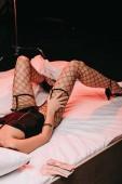 Ausgeschnittene Ansicht einer Frau in Strümpfen, die auf dem Bett in der Nähe von Dollarnoten auf schwarz liegt