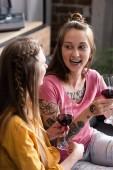 zwei Lesben halten Weingläser, während sie auf dem Sofa im Wohnzimmer sitzen