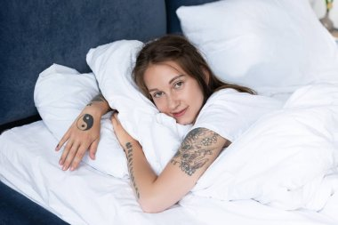 Attractive tattooed girl lying in bed and looking at camera in bedroom stock vector