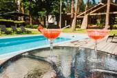 Cocktailgläser mit Alkoholcocktails auf Tisch in der Nähe des Schwimmbades