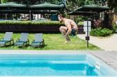 vista laterale delluomo barbuto con piedi nudi saltando in piscina