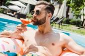 pohledný vousatý muž v brýlích s koktejlem