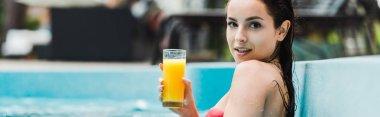 Panoramic shot of happy brunette girl holding glass of orange juice in swimming pool stock vector
