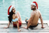 vidám férfi és nő a Mikulás kalapban ül a fából készült fedélzetek közelében medence