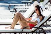 vonzó és stílusos nő Szalmakalapot és napszemüveget ül a nyugágyon