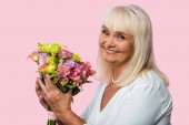 happy senior woman holding blooming flowers isolated on pink