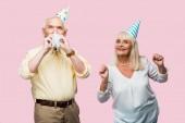 vezető férfi, amely arcát fél ventilátor közelében vidám feleség a párt sapka terhesség elszigetelt rózsaszín