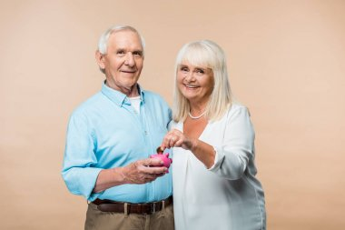 cheerful retired man holding pink piggy bank while senior wife putting coin isolated on beige
