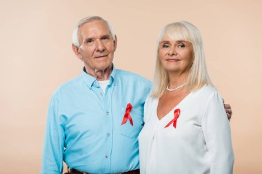 happy senior couple with red ribbons as hiv awareness isolated on beige