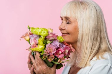 happy senior woman with closed eyes smelling bouquet of blooming flowers isolated on pink