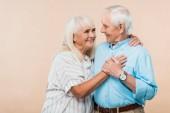 šťastná žena v důchodu s pohledem na veselého staršího muže izolovaného na béžové