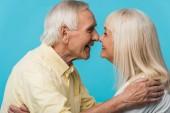 šťastný muž v důchodu, který se dívá na veselou ženu a směje se izolovaně na modrém