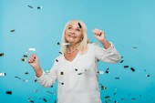 happy retired woman looking at falling confetti on blue